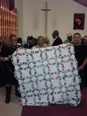Sam & Edith Johnson's daughters with Mrs. Teresa R. Kemp, (event keynote speaker) hold their mother's quilt at the African Diaspora Experience Scholarship Fundraiser & Exhibit on Feb. 7th, 2015 at the Hillside Presbyterian Church in Decatur, GA.