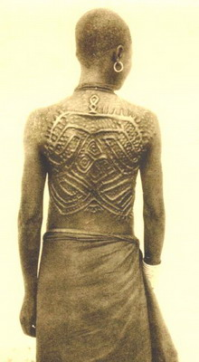 West African lady's back showing the scarification using the symbolic patterns of a language. These markings are not just designs.